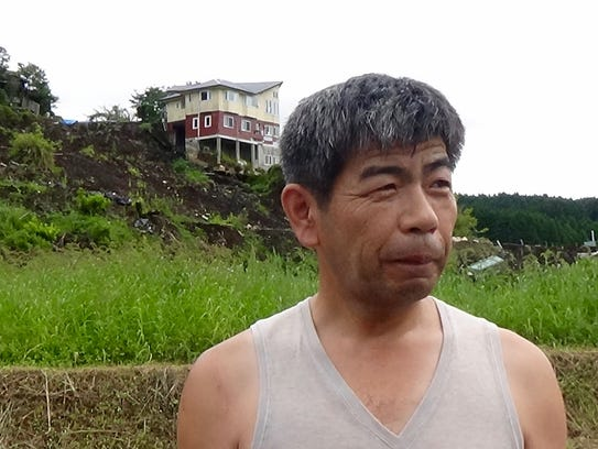 Hiroaki Morio, 52, stands in front of his ruined home