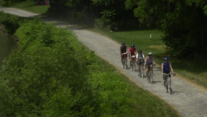 Cyclists make their way east on the Erie Canal path in Greece. A bike tour in Wayne County on Sept. 20 takes cyclists along the canal and past cobblestone houses.