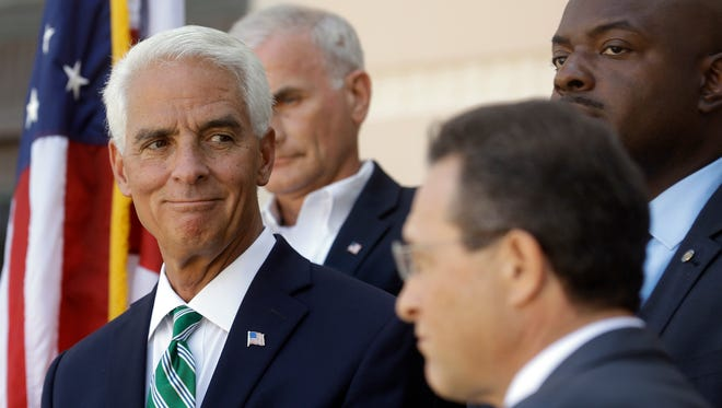 In this photo taken Aug. 17, 2016, former Florida Gov. Charlie Crist, left, smiles during a news conference in St. Petersburg, Fla. Crist is running as a Democrat for the U.S. House of Representatives for the 13th District in Florida.
