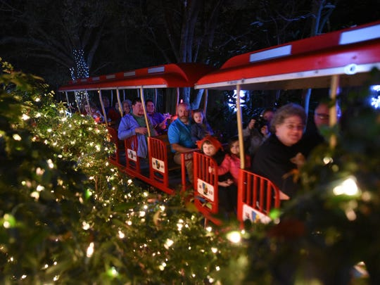Visitors ride the train in the Hattiesburg Zoo for the Zoo Lights and Holiday Market.