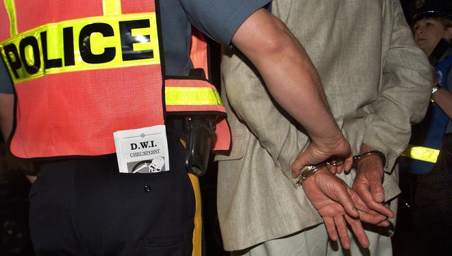 A suspected drunken driver is taken into custody at an area DWI checkpoint.