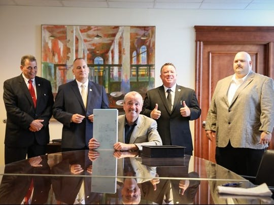 Gov. Phil Murphy poses with leaders of New Jersey's four major police and fire unions after signing a bill spinning off management of the police and fire pension fund in his Trenton office on July 3, 2018.