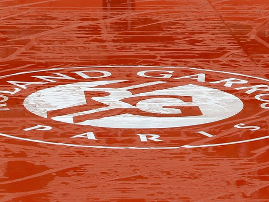 Puddles of rain water lie on the cover of center court of the French Open tennis tournament at the Roland Garros stadium in Paris, France, Monday, May 30, 2016. French Open organizers have announced the cancellation of all matches Monday at Roland Garros because of persistent rain forecast to last all day. (AP Photo/Michel Euler)