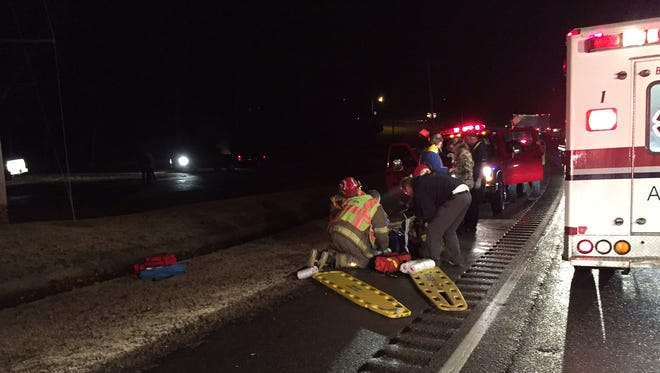 Emergency personnel treat a victim at the scene of a 2-car accident on U.S. 62 near the water tower in Cotter on Monday night.