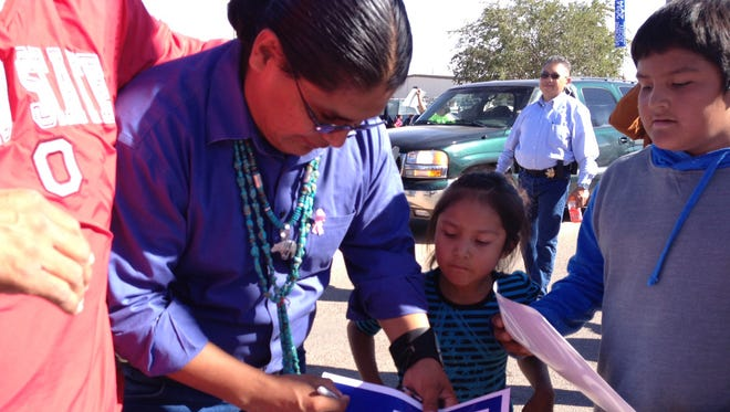 Disqualified Navajo presidential candidate Chris Deschene signs election placards at the 45th Western Navajo Nation Fair in 2014.