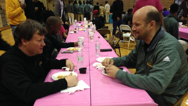 Byrd coach Rusty Johnson, left) and Captain Shreve coach Todd Martinez share a moment during Monday's event to raise cancer awareness at the school.