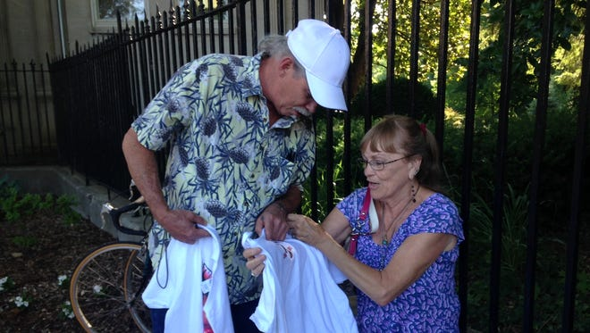 Todd Sexton shows wife Diane two Muhammad Ali T-shirts he purchased from a vendor Friday morning outside Cave Hill Cemetery. Avid fans of the boxer, the couple traveled from their home in Shelbyville, Indiana to witness Ali's funeral procession.
