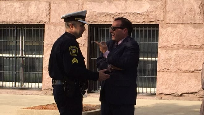 Mayor John Cranley and police union president Dan Hils talk before a press conference earlier this month promoting Cranley's plan to give raises to city workers, including police officers.