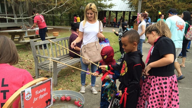Children go fishing for apples during Boo Bayou at Vermilionville.