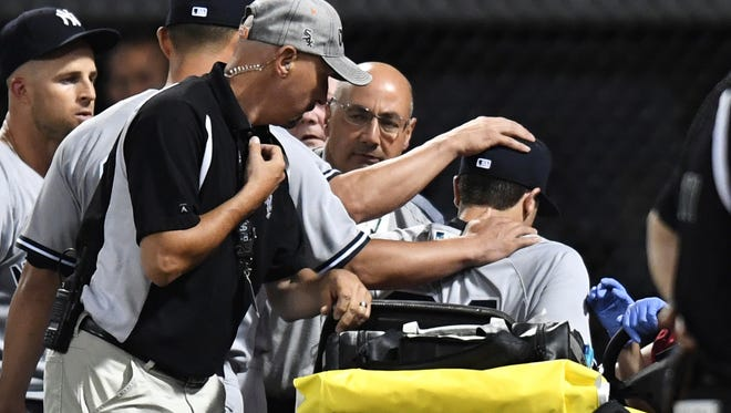 Players place their hands on New York Yankees right fielder Dustin Fowler (right) while being taken off the field after colliding with the wall in the first inning against the Chicago White Sox at Guaranteed Rate Field on Thursday, June 29, 2017.