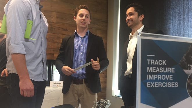 Matt Phifer (right) and Peter Fomin (center) of Fit Tech Labs chat at their company's table after giving their pitch at demo day.