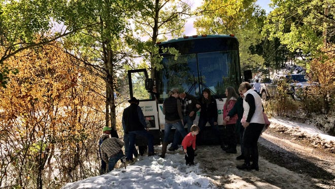 A team of helpers gets people off the bus, though the door opened to a significant drop-off.