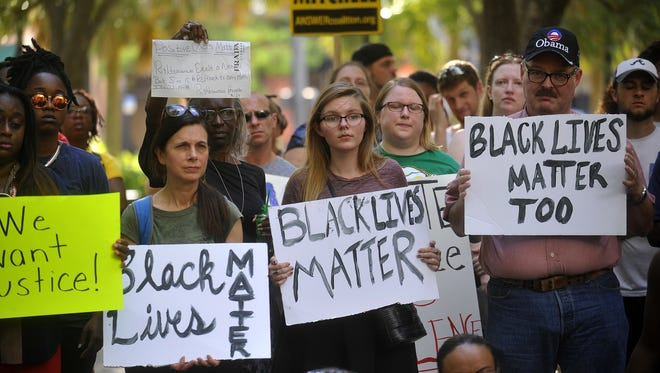 Protesters hold signs during a Black Lives Matter movement protest at Lykes Gaslight Park in downtown Tampa, Fla., Monday, July 11, 2016.
