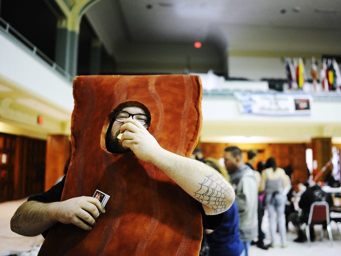 Dressed as a giant strip of bacon, Dan Lyso samples the Swedish pancake with bacon during the Sioux Falls Roller Dollz 5th annual Baconfest fundraiser on Saturday, April 26, 2014, at the Multicultural Center in downtown Sioux Falls. (Joe Ahlquist / Argus Leader)