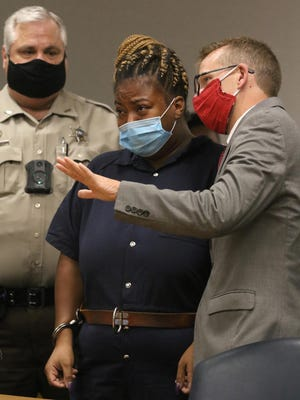 Public Defender Stuart Higdon speaks with Valencia McLean during her first appearance before District Court Judge Angela Hoyle on a first-degree murder charge Monday afternoon at the Gaston County Courthouse.