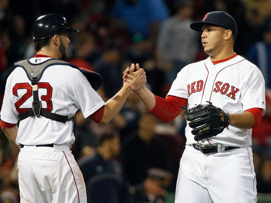 FILE - In this Sept. 26, 2015, file photo, Boston Red Sox's Jonathan Aro, right, and Blake Swihart (23) celebrate after defeating the Baltimore Orioles 8-0 in a baseball game in Boston. The Seattle Mariners have obtained left-hander Wade Miley and reliever Jonathan Aro from the Boston Red Sox for reliever Carson Smith and pitcher Roenis Elias, Monday, Dec. 7, 2015. (AP Photo/Michael Dwyer, File)