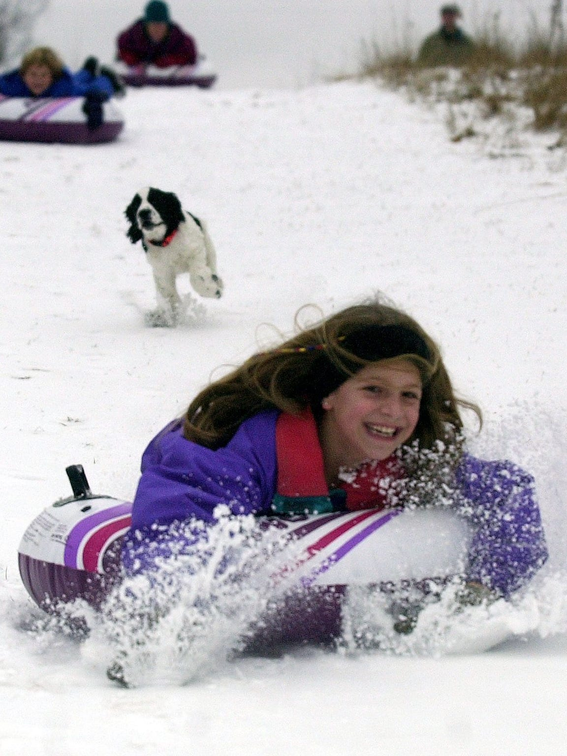 Sarah Martin, of Wausau, zooms down a hill near Sylvan Hill park in 2002 as Damon Cronce's dog, Spencer, chases her while sledding with her brother Adam and her mother, Laura.