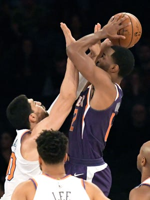 New York Knicks center Enes Kanter, left, gets a hand in the face of Phoenix Suns forward TJ Warren (12) during the first quarter of an NBA basketball game Friday, Nov. 3, 2017, at Madison Square Garden in New York. (