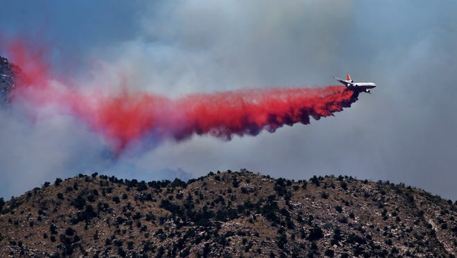 A plane drops fire retardant on top of the Burro Fire near Burro tank outside Tucson.