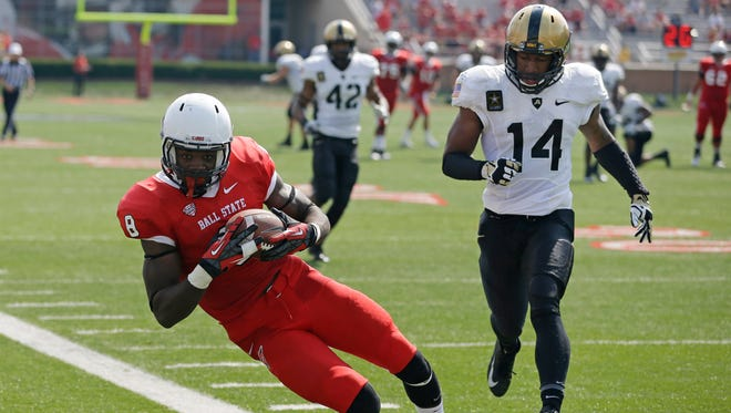 Ball State wide receiver Jordan Williams , left, gets his foot down in bounds as he makes a catch in front of Army defensive back Steven Johnson during the second half of an NCAA college football game in Muncie, Ind., Saturday, Sept. 7, 2013. Ball State defeated Army 40-14.  (AP Photo/Michael Conroy)
