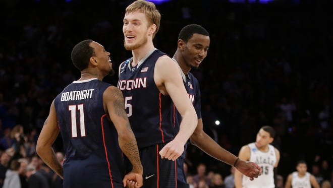 Connecticut's Ryan Boatright, left,, Niels Giffey, center, of Germany, and DeAndre Daniels, right, celebrate.
