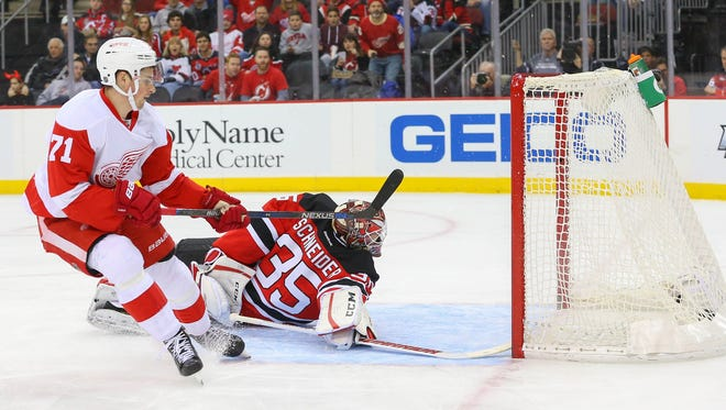 Red Wings center Dylan Larkin (71) scores a goal on Devils goalie Cory Schneider (35) during the first period of the Wings' 1-0 win Monday at Newark, N.J.