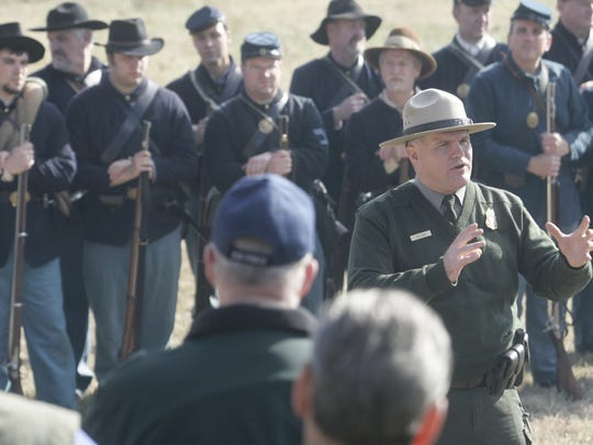 Park Ranger Jim Lewis talks about the Battle of Stones River as he is surrounded by re-enactors during a previous battle anniversary.