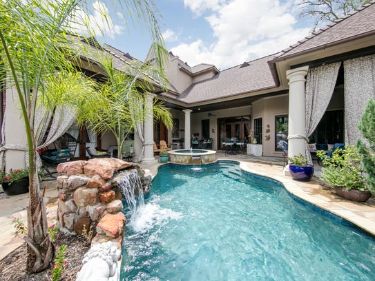 The inviting pool includes a hot tub and waterfall.