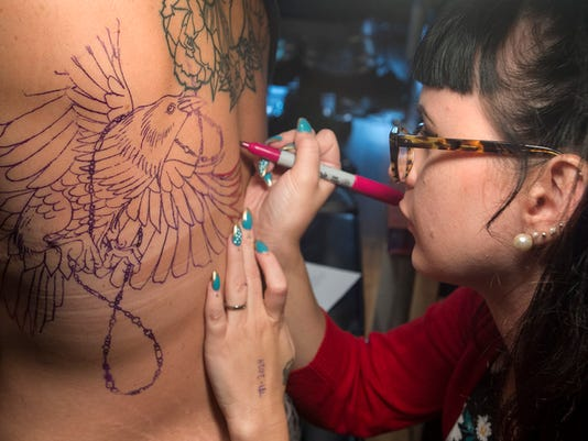 Sadie Swartz works on a raven on a back at Euphoria Tattoo Emporium in the 100 block of North George Street in York.