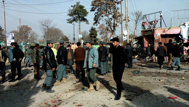 Afghan police forces and civilians inspect the site of a suicide attack in Maymana, capital of Faryab province, Afghanistan, on March 18.