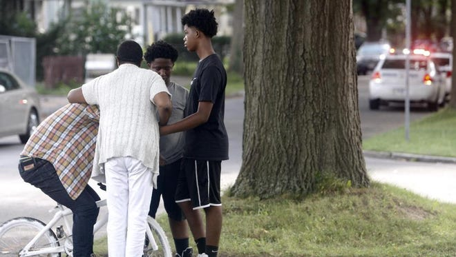 Rev. Marilyn Cunnigham of Graves Memorial CME, consoles people near the scene of the shooting.