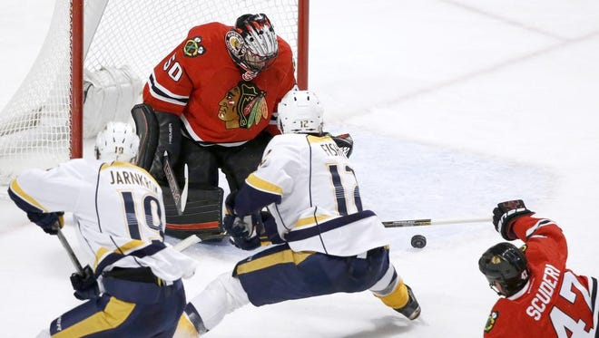 Blackhawks goalie Corey Crawford makes a save on a shot by Predators center Mike Fisher (12) as Calle Jarnkrok (19) and Rob Scuderi look for a rebound during the second period Tuesday in Chicago.