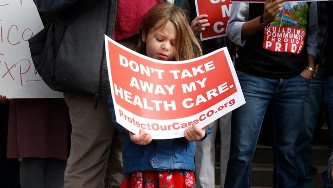 Girl holds sign protesting GOP plan to dissolve Colorado's Affordable Care Act exchange, Denver, Jan. 31, 2017.