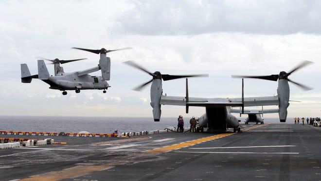 In this June 29, 2017, file photo, Marine MV-22B Osprey aircraft land on the deck of the USS Bonhomme Richard amphibious assault ship off the coast from Sydney. A MV-22 Osprey that launched from the USS Bonhomme was conducting regularly scheduled operations when it crashed into the water off Australia's east coast Aug. 5.