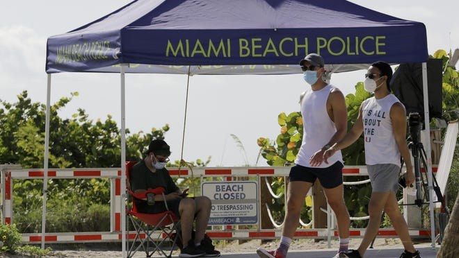 People wearing protective face masks walk past a closed entrance to the beach during the new coronavirus pandemic, Friday, July 3, 2020, in the South Beach neighborhood of Miami Beach, Fla. Beaches throughout South Florida are closed for the busy Fourth of July weekend to avoid further spread of the new coronavirus.