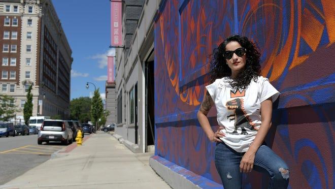 Em Quiles stands near ArtsWorcester on Portland Street on Monday.