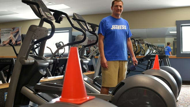 Tim MacDonald of Worcester Fitness prepares Tuesday for reopening. Some gym machines haven't been plugged in and cones have been placed on them to ensure proper social distancing.