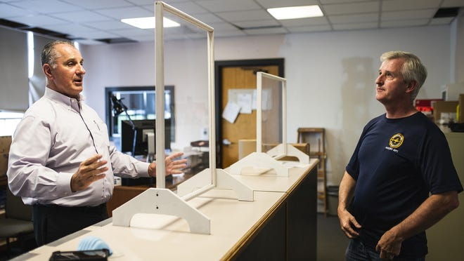 From left, Rob Pezzella, Worcester Public School's COVID-19 response facilitator, and Paul Comerford from the facility department show off the Plexiglas shields that will be used in the school systems office and administration buildings when students return to schools in the fall.