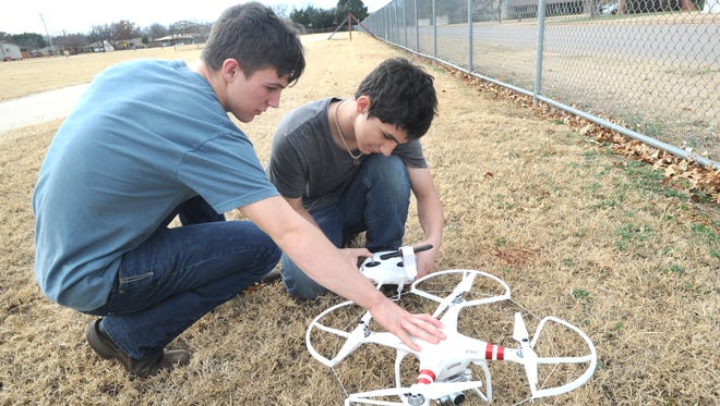 Braedyn Beall, left, and Michael Beall set up their new Phantom 3 drone in the field at Austin Elementary School Monday.