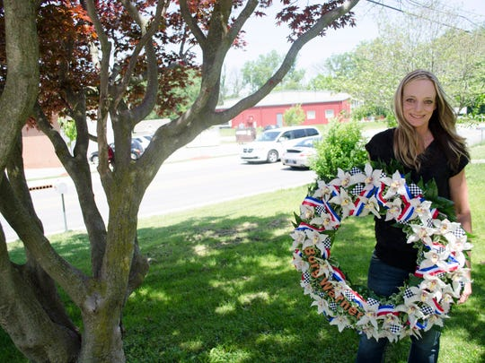 Julie Harman-Vance, a Yorktown florist, poses with the handcrafted BorgWarner wreath for the Indianapolis 500 outside her shop.