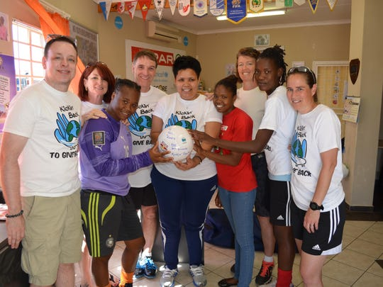 Children and program directors in Namibia present Kickin' Back with a signed soccer ball as a thank you gift.