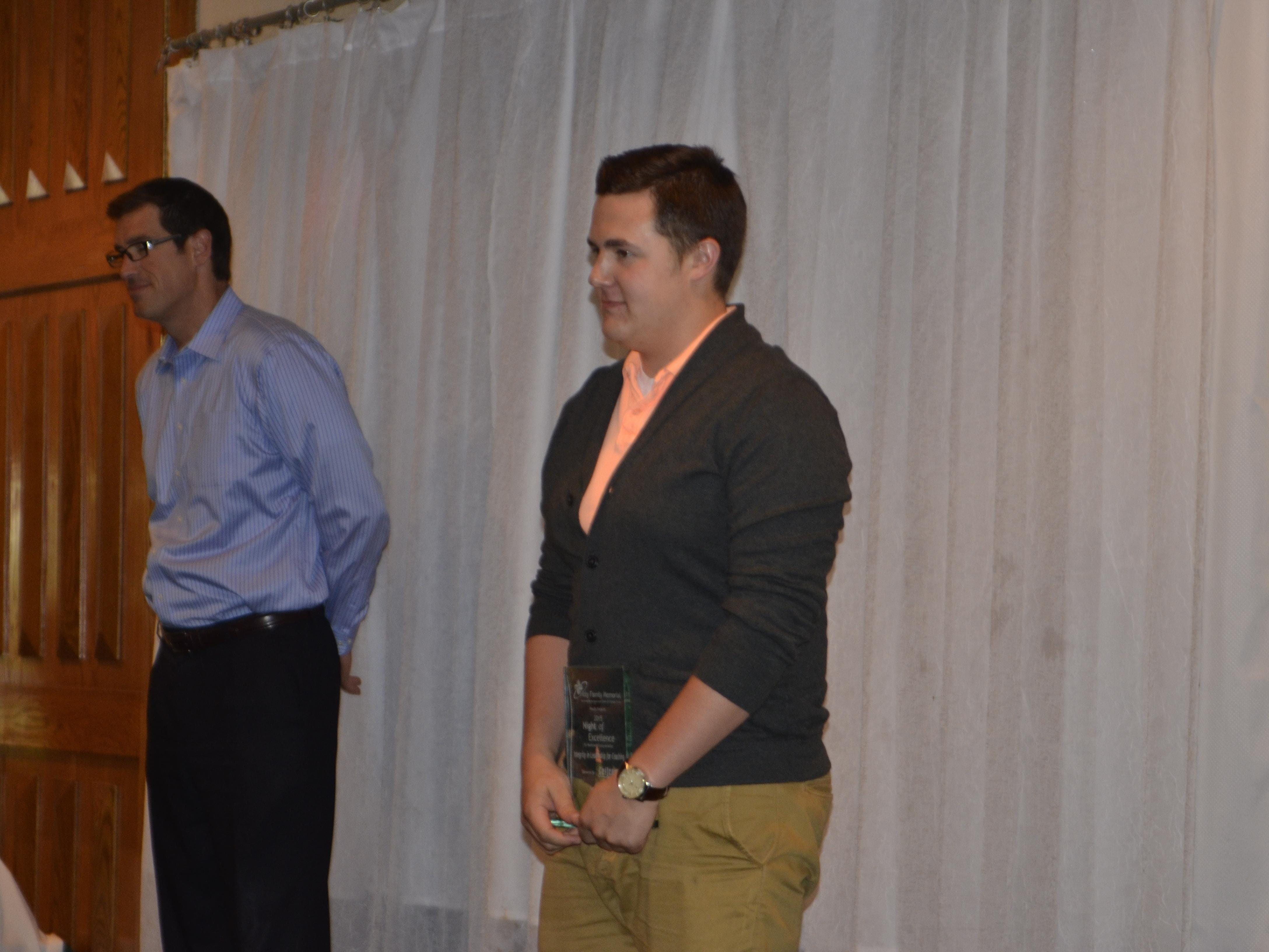 Drew Dixon accepts the Integrity in Coaching award for his late father and former Manitowoc Lincoln football coach John Dixon at Wednesday's Holy Family Memorial Night of Excellence awards banquet at Fox Hills in Mishicot.