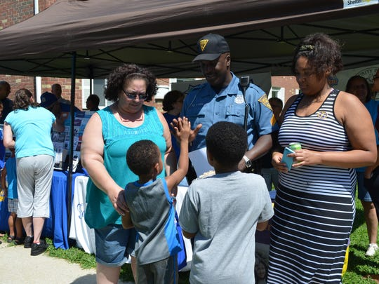 Sgt. Shane Harris of the Vineland Police Department Juvenile Unit talks with Edith Moya, Jimmy Travis, 7, Jacob Travis, 5, and Samantha Marty, all of Vineland during the Dog Days of Summer event at the Arbors on Main apartment complex, 821 N. Main Rd., on Saturday.