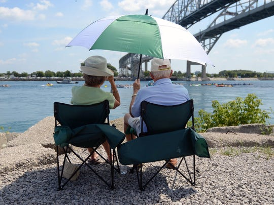 Jeanne and Julian Sullivan, of St. Clair, sit under their umbrella and watch the floaters pass by Sunday during the annual float down in the St. Clair River.