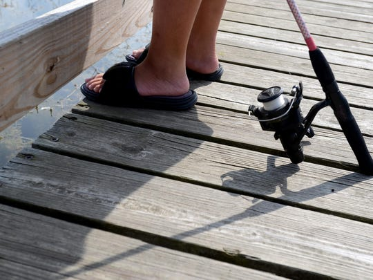 Eric Compton, 12, of Port Huron, stands on the dock to fish Monday, Aug 17, at 40th Street Pond.