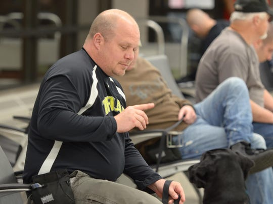 Wade Baker works with Honor, his service dog from the Paws & Effect organization in Iowa.