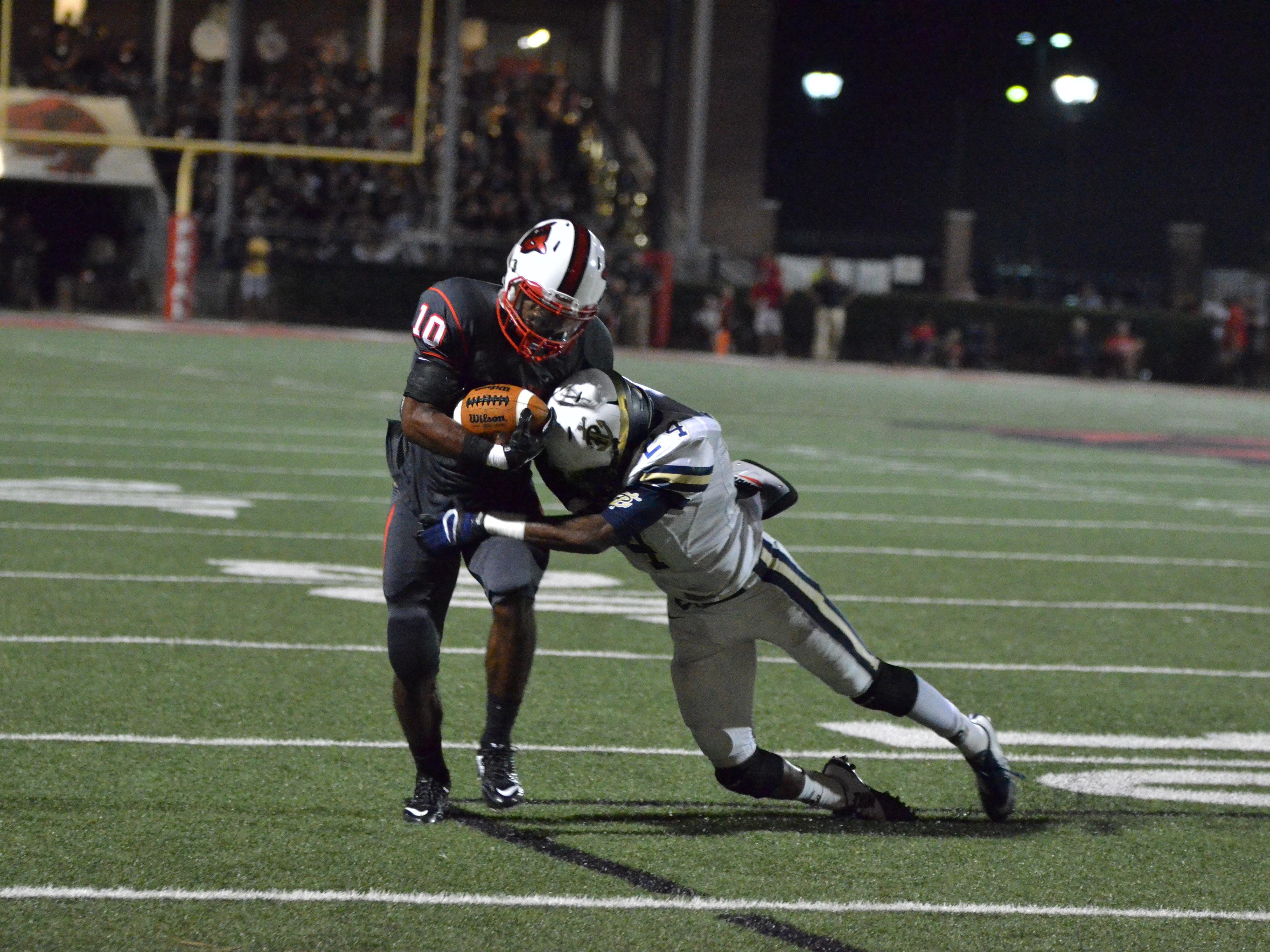 Petal's Tanner Estill tries to break a tackle by Pearl's Kameron Spann Friday night during their game at Petal.