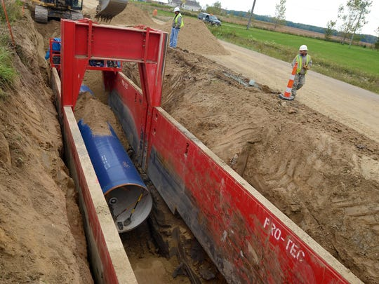 Pipeline is laid into the ground Monday, Oct. 5, along Fisher Road in Grant Township.