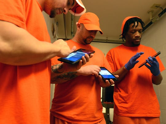 Inmate Eric McCall, right, plays on his new tablet Mondayat the Sanilac County jail in Sandusky. Inmates are using these on a free trial basis at the jail.