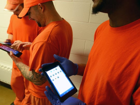 A group of inmates scroll through their new tablets Monday, Dec. 28, at the Sanilac County jail in Sandusky.